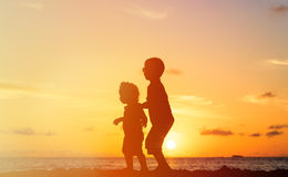 Little boy and girl walking at sunset Royalty Free Stock Images