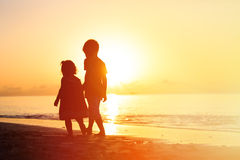 Little boy and girl walking on sunset beach Stock Photos