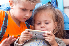 Little boy and girl watching cartoon on mobile device Royalty Free Stock Photography
