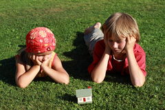 Little boy and girl watching a house. Little boy and girl lying on the grass and watching a model of a house royalty free stock images