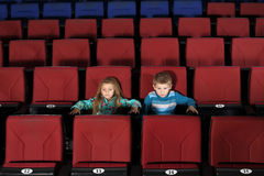 Little boy and girl watching a movie in empty cinema Stock Photo