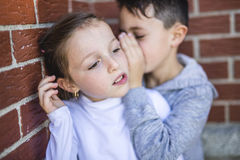 Little boy and girl whispers a secret. stock photography