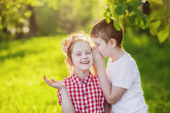 Little boy and girl whispers. Stock Image