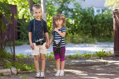 Little boy and a little girl wit two vintage cameras standing to. Gether holding hands Royalty Free Stock Images