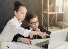 Little boy and girl working on laptop. Little professionals in office. Small boy and girl browsing on laptop, teamwork, copy space stock images
