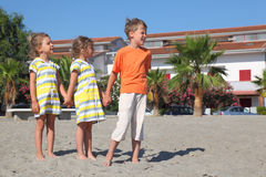 Little boy and girls standing on beach Stock Photo