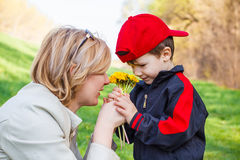 Little boy give flower to mom. Happy mother and cute son with dandelions, outdoor Royalty Free Stock Photo