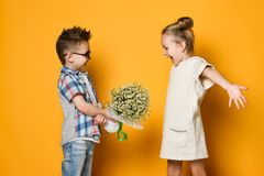 Happy caucasian people boy gives a flowers to his girlfriend isolated over yellow background. A little boy gives a bouquet of daisies to his girlfriend a girl stock photo
