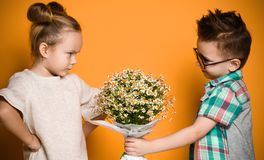 Little boy gives a bouquet of daisies to his girlfriend a girl. The girl angrily folded her arms in front of her and did not want to take a gift. Concept of stock photo