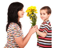 Little boy gives flowers to his mom. Little boy gives yellow flowers to his mom isolated on white stock photo