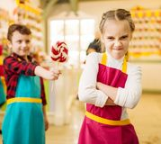 Boy gives handmade lollipop to stubborn girl. Little boy gives handmade lollipop to stubborn girl. Children in workshop at pastry shop. Holiday fun in candy Royalty Free Stock Image