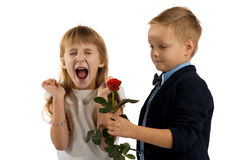Little boy gives a red rose to girlfriend. Stock Image
