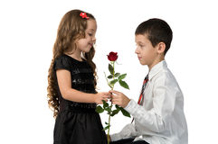 Little boy gives a red rose to girlfriend. relationship between Royalty Free Stock Images