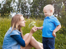 The little boy gives to mum wild flowers. In nature stock images