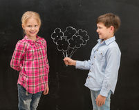 Little boy givig drawn flowers to the smiling  girl Stock Image