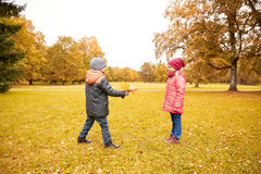 Little boy giving autumn maple leaves to girl Royalty Free Stock Image