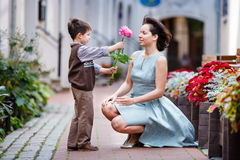 Little boy giving flower to his mom. In city street Stock Photos