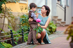 Little boy giving flower to his mom. In city street Royalty Free Stock Images