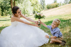 Little boy giving flower to his mom. The boy gives flowers to the bride, his mother stock photography