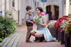 Little boy giving flower to his mom. Outdoors Stock Photos