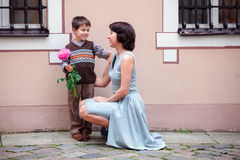 Little boy giving flower to his mom. Outdoors Stock Photography