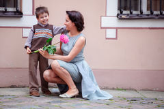 Little boy giving flower to his mom. Outdoors Stock Images
