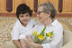 Little boy giving flowers to his grandmother Stock Images