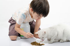 Little boy giving food for cat. On the floor Stock Photos