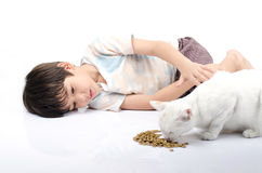 Little boy giving food for cat Royalty Free Stock Photo