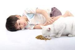 Little boy giving food for cat Stock Photos