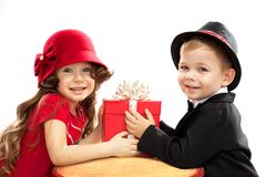 Little boy giving girl gift. Present for a birthday, valentine's day, birthday or other holiday. Isolated on white background Royalty Free Stock Photos
