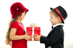 Little boy giving girl gift. Present for a birthday, valentine's day, birthday or other holiday. Isolated on white background Royalty Free Stock Image