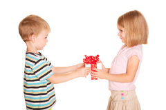 Little boy giving a little girl a gift. Little kids friendship and love. Little boy giving a little girl a gift. Present for a birthday, valentine's day or Royalty Free Stock Image