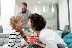 Little Boy Giving Presents to Mom. Side view portrait of adorable little boy giving present to his mom on Valentines day, with father in background Royalty Free Stock Photo