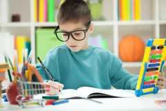 Little boy with glasess at home studying Royalty Free Stock Photo