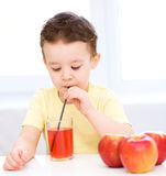 Little boy with glass of apple juice Stock Images