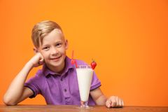 Little boy with glass of milk shake at table. On color background royalty free stock photo