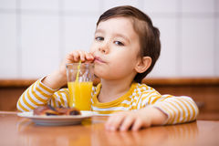 Little boy with glass of orange juice Stock Images
