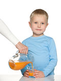 Little boy with a glass of orange juice Stock Photos