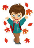 Little boy with glasses and backpack playing with autumn leaves Royalty Free Stock Images