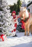 Little boy with glasses caresses adorable pony with festive wreath near the small wooden house and snow-covered trees. New Year an stock photos