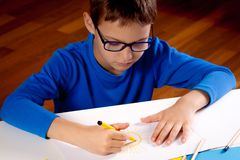Little boy with glasses drawing with colored pencils and felt pens Royalty Free Stock Photos
