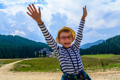 Little boy in glasses and a hat in a background of mountains and Stock Photos