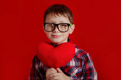 Little boy in glasses with a heart of toy Royalty Free Stock Image