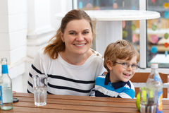 Little boy with glasses and his mother enjoying drinks Royalty Free Stock Images