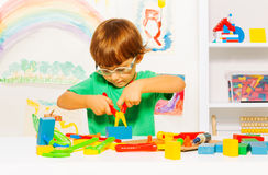 Little boy in glasses learning to use pliers Stock Photo