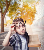 Little boy in glasses reads book on city street Stock Image