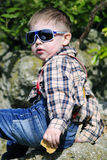 Little boy with glasses on the rocks Stock Photo