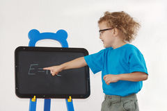 Little boy with glasses shows Einstein's formula Stock Images