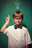 Little boy with glasses standing in front of chalkboard with bul Royalty Free Stock Photography